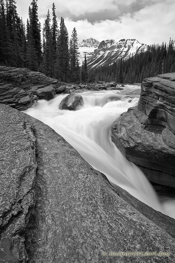Water runs fast through Mistaya Canyon in the spring during the snow melt. - Canada Photography