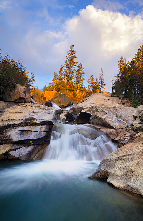 The soothing swoosh of the waterfall was the other sound as the warm last light strikes trees above the Grottos Waterfall in the White River National Forest in Colorado. - Colorado Photography