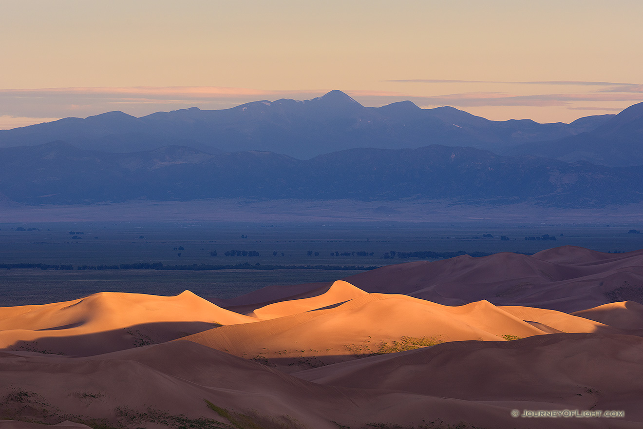 Light graces the tops of the Sand Dunes in the distance as the sun peaks over the Sangre De Cristo range. - Great Sand Dunes NP Picture