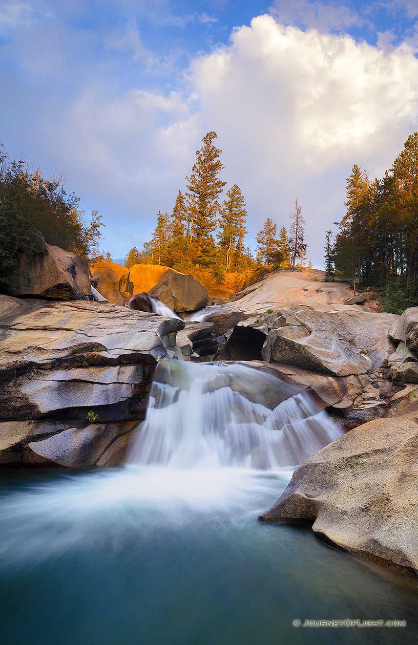 The soothing swoosh of the waterfall was the other sound as the warm last light strikes trees above the Grottos Waterfall in the White River National Forest in Colorado. - Colorado Picture