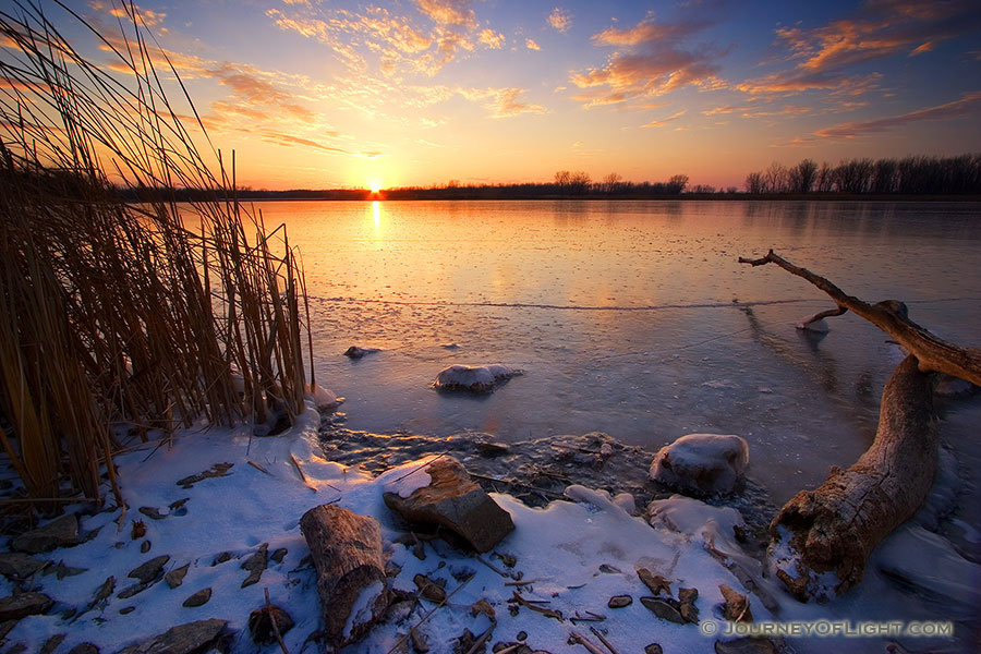 The sun reflects off a frozen lake in DeSoto National Wildlife Refuge in eastern Nebraska. - DeSoto Photography