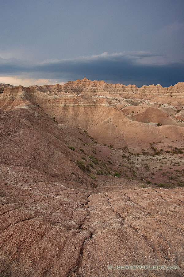 As a storm passes over Badlands National Park in South Dakota, dark clouds contrast with the desolate landscape. - South Dakota Photography