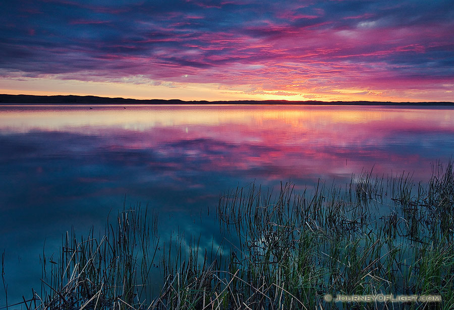 A small lake nestled in the Sandhills reflects the rising sun on a cool spring morning. - Valentine Photography