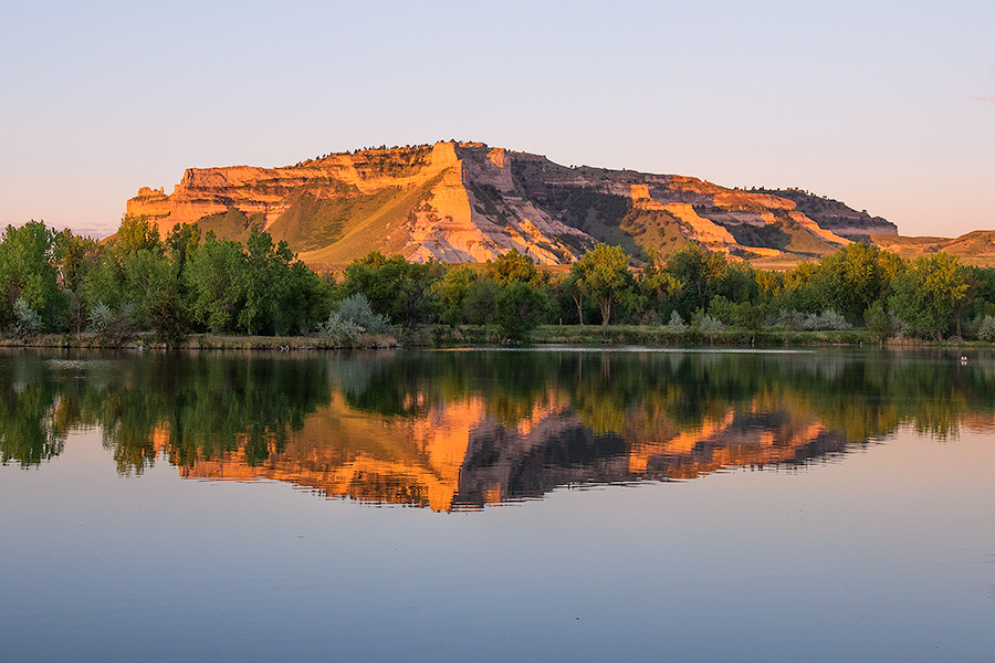 Glowing in the light of the recently risen sun, Scotts Bluff National Monument in western Nebraska is reflected in a small nearby lake. - Nebraska Photography