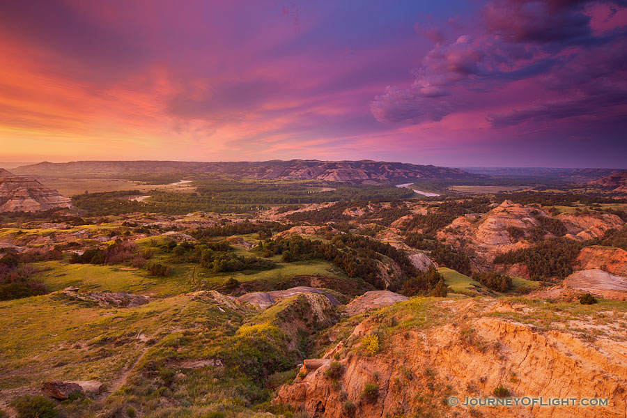 Above a bend in the Little Missouri River in the North Unit of Theodore Roosevelt National Park, clouds glow purple and orange as the sun just begins to rise above the horizon. - North Dakota Photography