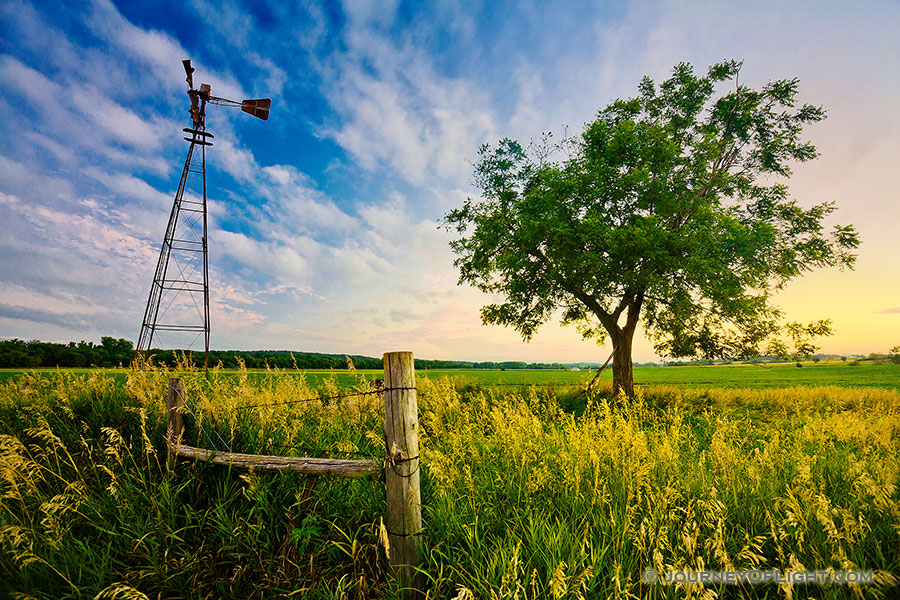 An old windmill and fence are the only company to a single tree on the eastern Nebraska plains. - Nebraska Photography