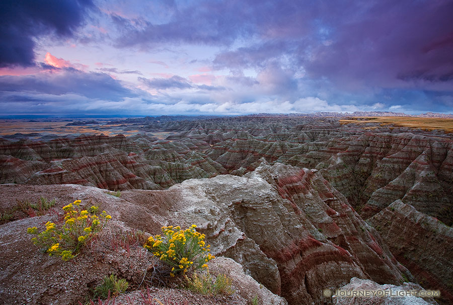 On a cool morning, the smell of a past rain fills the air.  The sunrise illuminates the passing storm clouds at Badlands National Park, South Dakota. - Badlands NP Photography