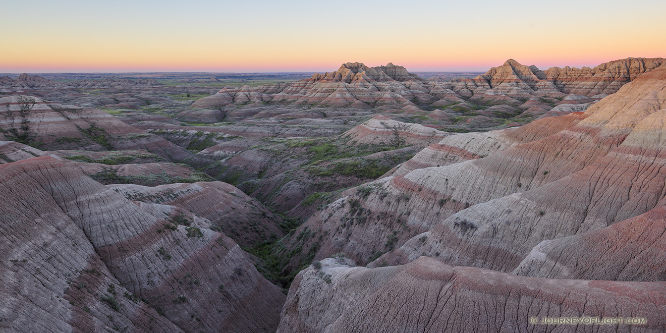 A panoramic scenic photograph of the sunrise over the Badlands National Park, South Dakota. - South Dakota Picture