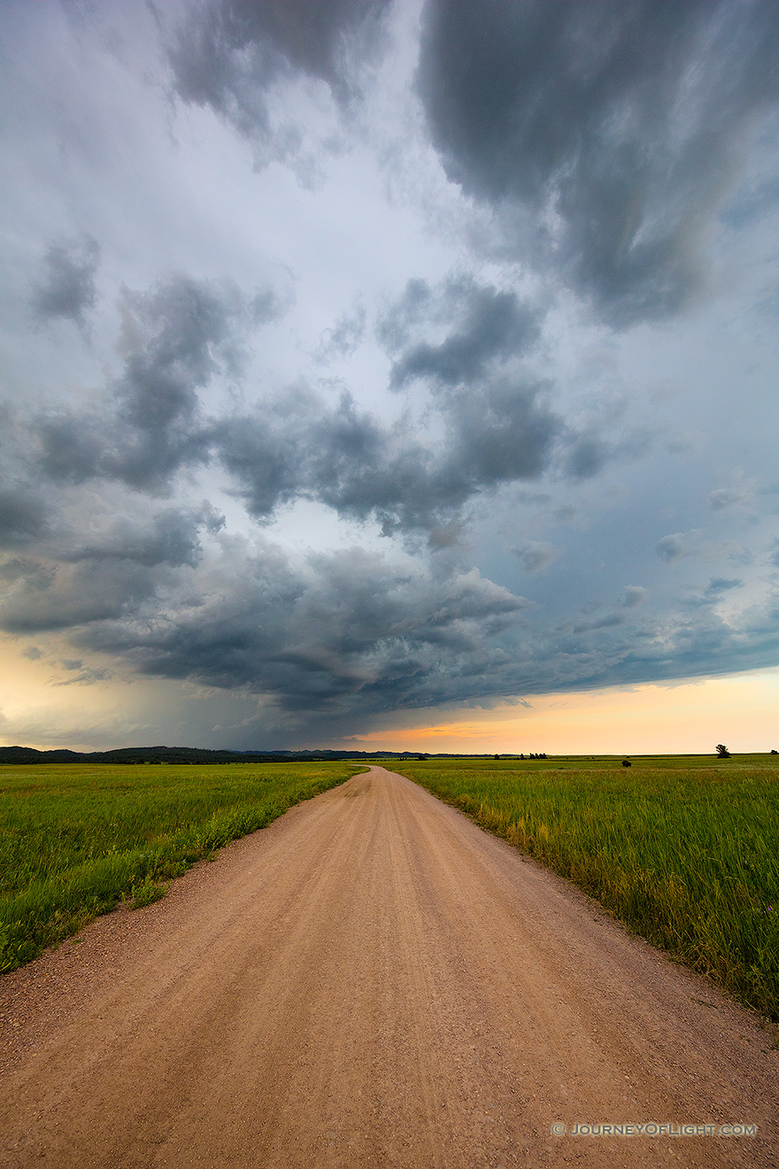 A landscape photograph of an intense summer storm rages over a rural country road in South Dakota. - South Dakota Picture