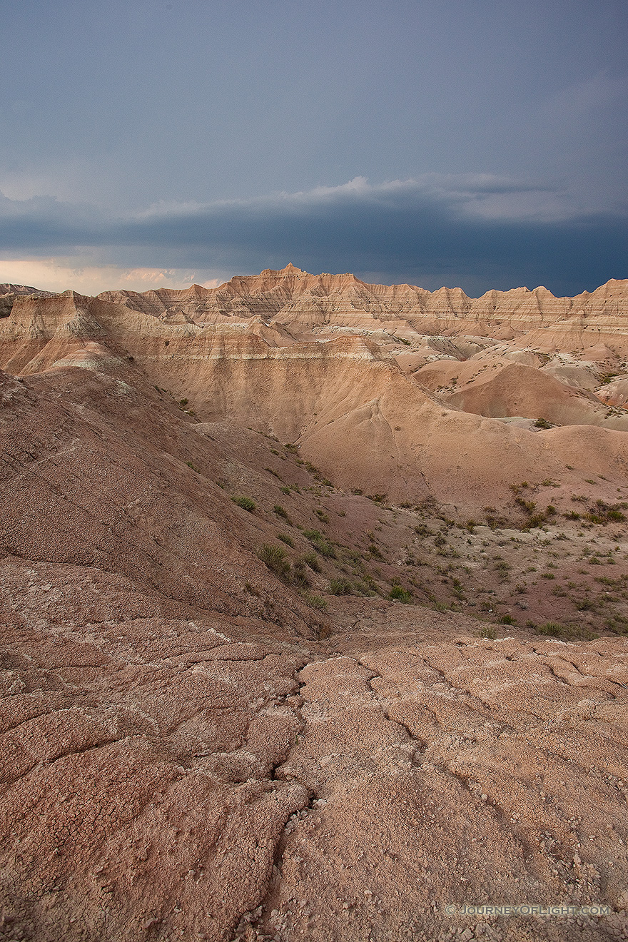 As a storm passes over Badlands National Park in South Dakota, dark clouds contrast with the desolate landscape. - South Dakota Picture