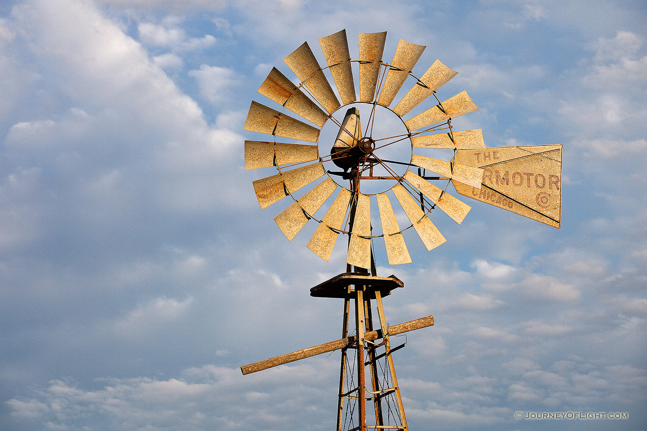 In rural Dixon County in Northeastern Nebraska a still windmill reflects the golden light of the rising sun against a cloudy sky. - Nebraska Picture