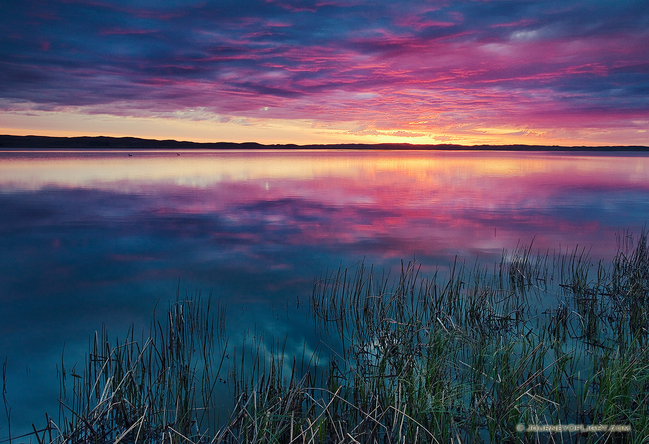 A small lake nestled in the Sandhills reflects the rising sun on a cool spring morning. - Valentine Picture