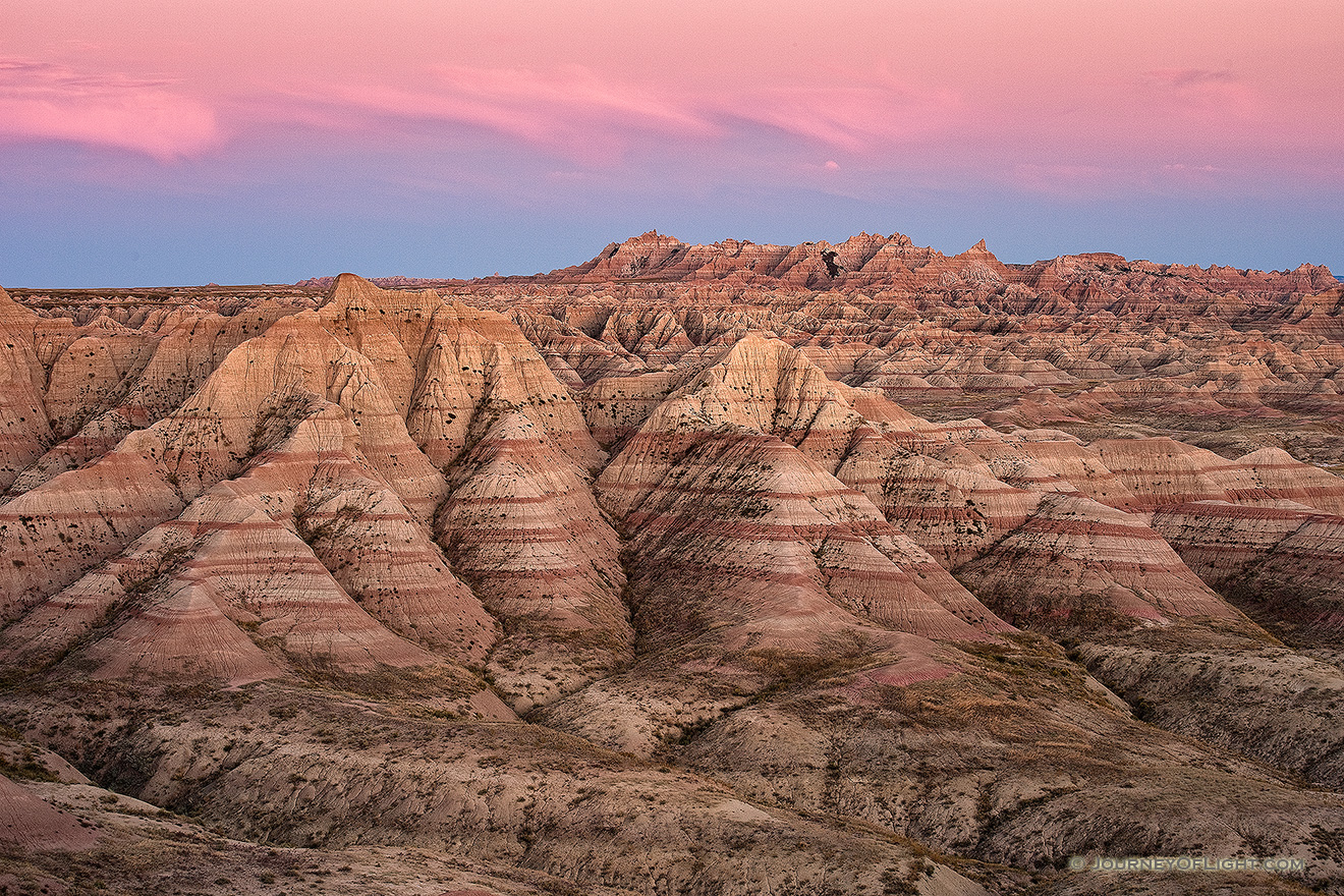 Pink clouds float above Badlands National Park while the rocky terrain below is bathed in the warm light just after sunset. - South Dakota Picture