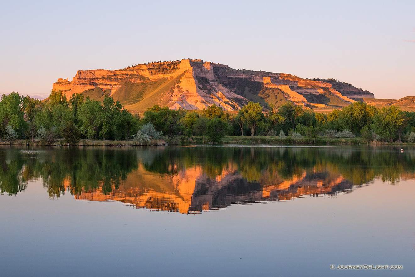 Glowing in the light of the recently risen sun, Scotts Bluff National Monument in western Nebraska is reflected in a small nearby lake. - Nebraska Picture