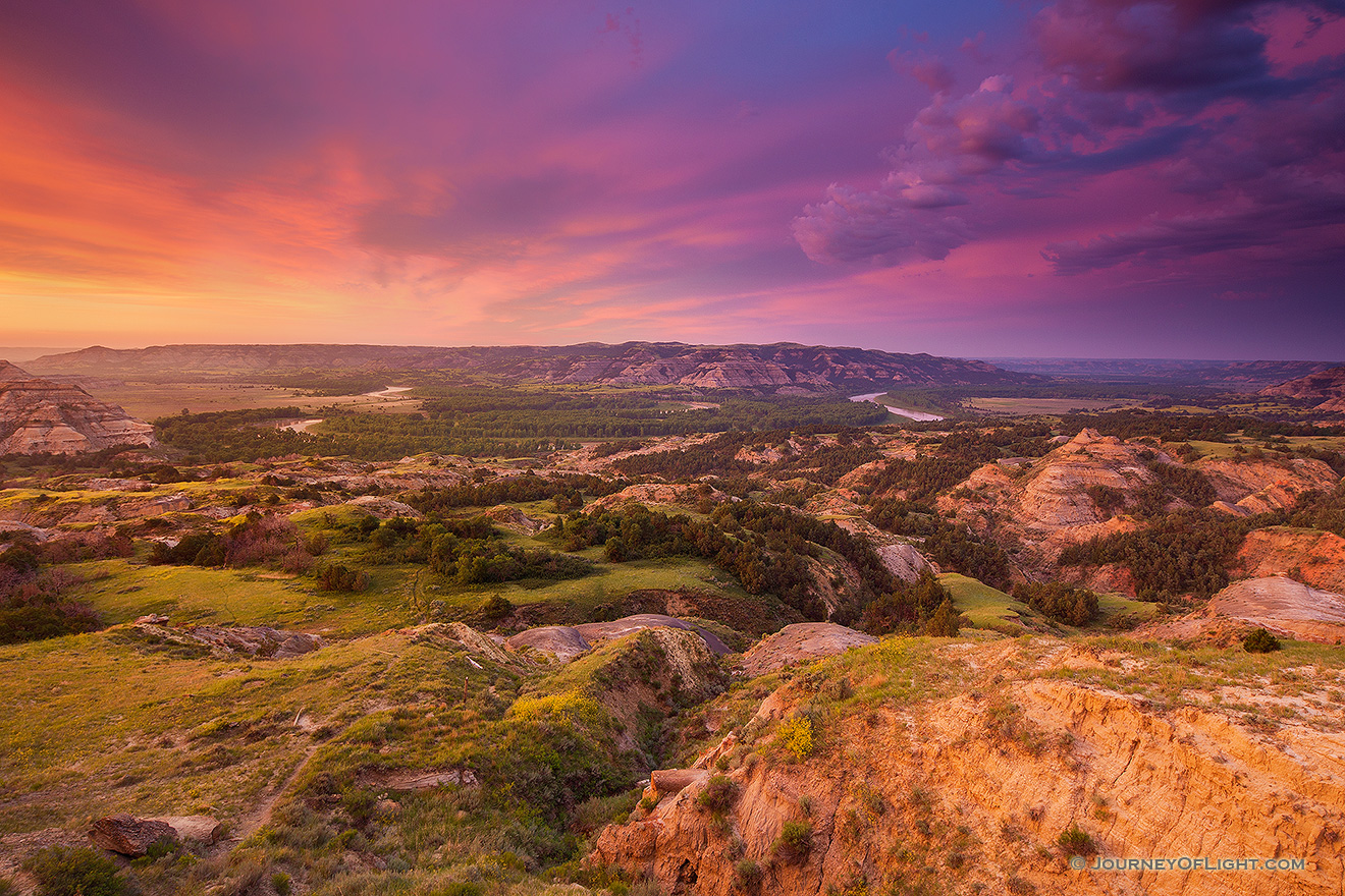 Above a bend in the Little Missouri River in the North Unit of Theodore Roosevelt National Park, clouds glow purple and orange as the sun just begins to rise above the horizon. - North Dakota Picture