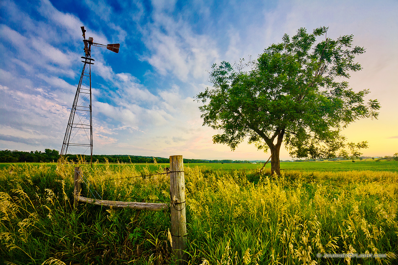 An old windmill and fence are the only company to a single tree on the eastern Nebraska plains. - Nebraska Picture