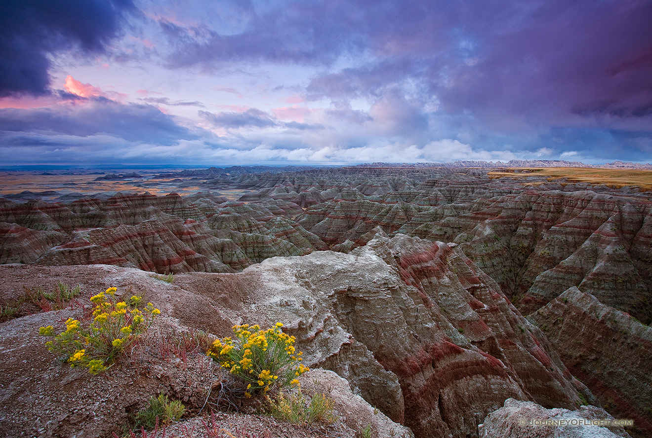 On a cool morning, the smell of a past rain fills the air.  The sunrise illuminates the passing storm clouds at Badlands National Park, South Dakota. - Badlands NP Picture