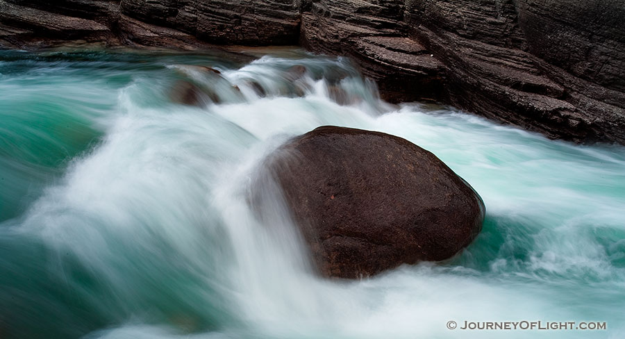 A lone rock holds against the rush of the water at Maligne Canyon in Banff National Park, Alberta, Canada. - Banff Photography