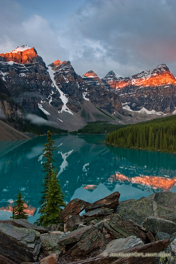One of the most scenic and popular destinations in Banff National Park, Lake Moraine reflects the ten peaks on fire with an early morning glow.  Around 3:30 in the morning I rose to get to Lake Moraine for a 6:00 sunrise.  Since I was 60 miles away, I had to make sure to give myself enough time to get there and get set up.  This scene was my reward. - Banff Photography