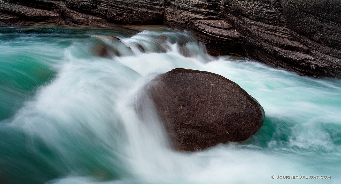 A lone rock holds against the rush of the water at Maligne Canyon in Banff National Park, Alberta, Canada. - Banff Picture