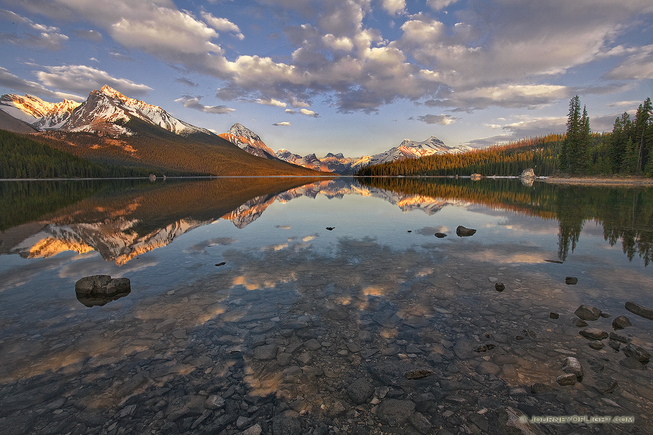 Clouds float lazily down the water as the last light hits at Maligne Lake located in Jasper National Park. - Canada Picture